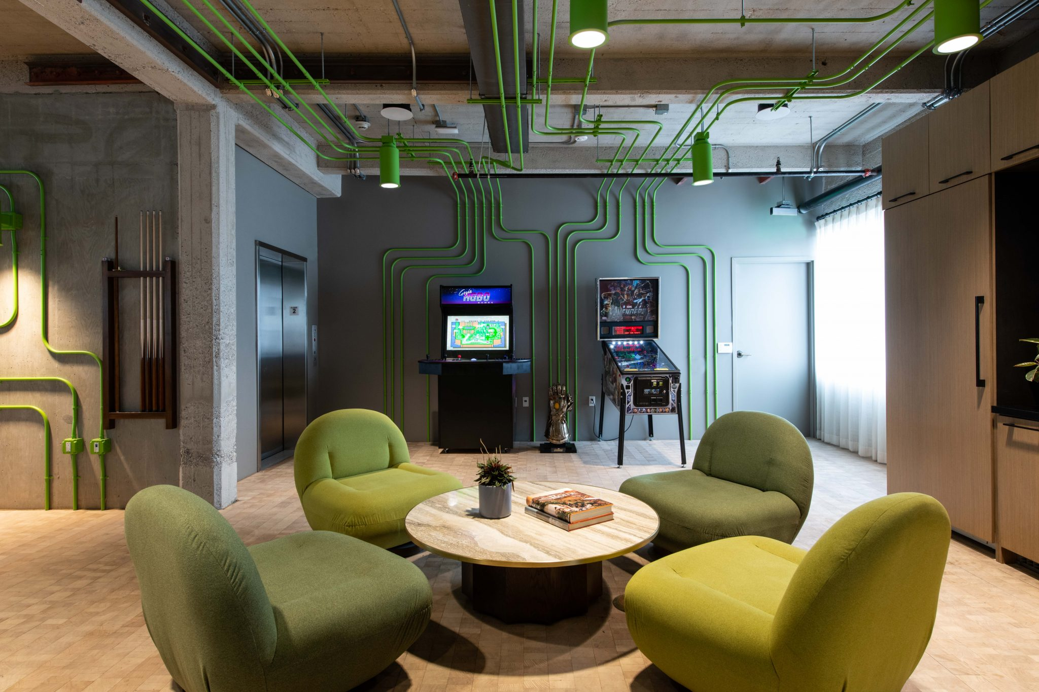 Work lounge. Arcade machine and pinball. Green upholstered chairs.LA shared workspace, DDI Designs